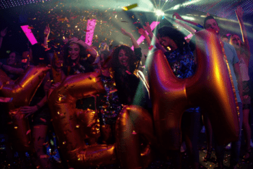 party friends in night club with yeah balloons and confetti rlpz7udwx thumbnail full01